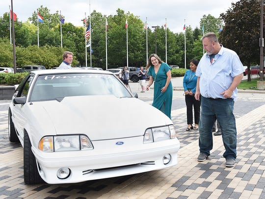 Wesley Ryan of San Antonio, right, along with his family, from left, son Jacob Ryan, daughter Jeni Ryan and wife Laura, check out his 1993 Mustang GT, which he had sold 17 years ago to pay for his wife's cancer treatment. Ford restored the long-lost car after Jacob and Jeni tracked it down.