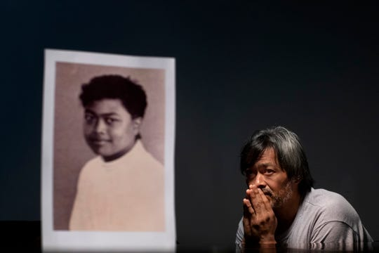 Mark Apuron, 45, sits beside a photo of himself when he was 15 years old, the age when he says he was raped by his uncle, former Archbishop Anthony Apuron at the rectory, in Hagatna, Guam.