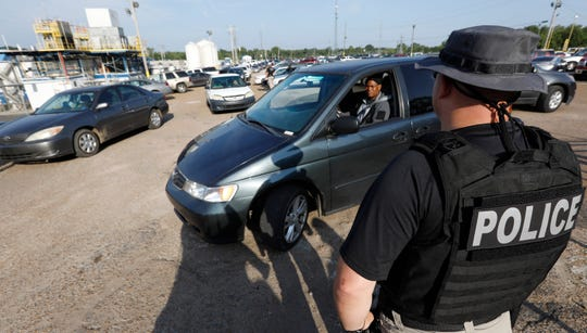 A federal agent directs a vehicle to approach as they begin to clean out the parking lot at a Koch Foods Inc., plant in Morton, Miss., Wednesday, Aug. 7, 2019. The agent was one of many who participated in the early morning raid that was part of a large-scale operation targeting owners as well as undocumented employees.