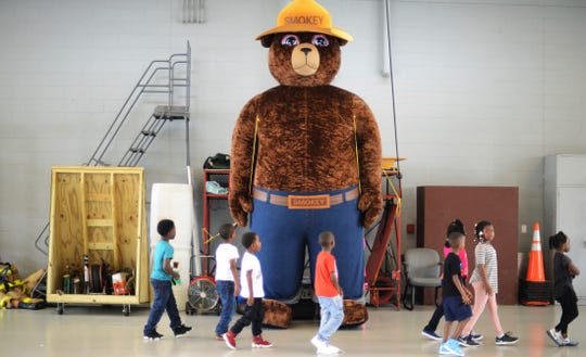 FILE - In this Wednesday, Oct. 11, 2017 file photo, a giant Smokey Bear statue greets children at the Fire Department Open House at Fire Station One in Kinston, N.C. The icon of the longest-running public service campaign in the U.S., was born on Aug. 9, 1944, when the U.S. Forest Service and the Ad Council agreed that a fictional bear would be the symbol for a fire prevention campaign.