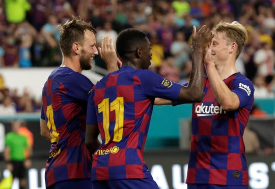 Barcelona's Ivan Rakitic (4) celebrates with Ousmane Dembele (11) and an unidentified teammate after scoring a goal against Napoli during the second half Wednesday in Miami Gardens, Fla. Barcelona won 2-1.