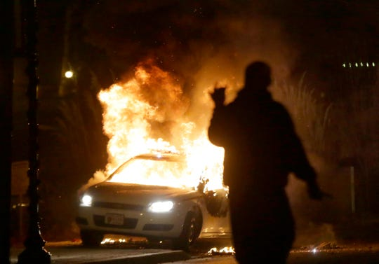 In this Nov. 24, 2014, file photo, a police car is set on fire amid protests that followed the announcement that a grand jury had declined to indict Ferguson police officer Darren Wilson in the death of Michael Brown.