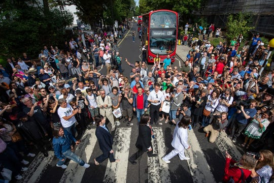 Beatles lookalikes are joined by thousands of fans gathered to walk across the Abbey Road zebra crossing, on the 50th anniversary of British pop musicians The Beatles doing it for the cover of their album 'Abbey Road' in St Johns Wood in London, Thursday, Aug. 8, 2019.