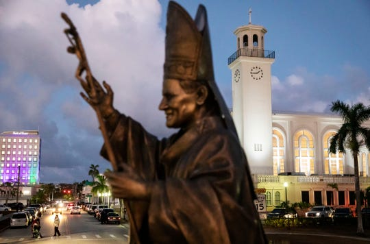 A statue of Pope John Paul II stands outside the island's main cathedral, Dulce Nombre de Maria Cathedral-Basilica, during a Mass in Hagatna, Guam, Tuesday, May 7, 2019.