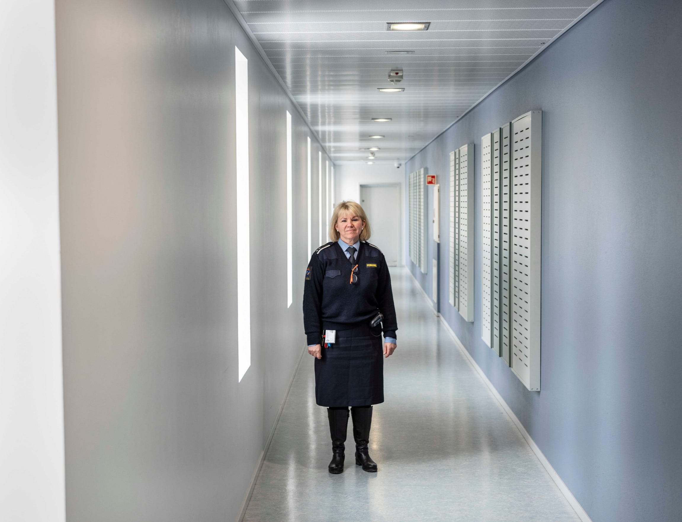 Works manager Janne Hasle stands in a light-filled corridor at Halden Prison in Norway, where inmates live in dorm-like rooms in three buildings on a campus filled with trees.