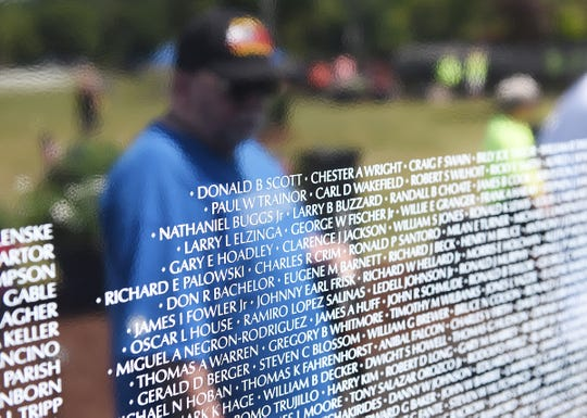 Jeff Brown, 60, of Flat Rock, is reflected in the Moving Wall Vietnam Veterans Memorial as he views it at Livonia's Ford Field Thursday.