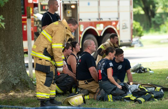 Firefighters take a break after fighting a fire at 1821 Asbury Drive in Evansville Thursday afternoon. German, McCutchanville and Scott townships all had personnel on-scene.