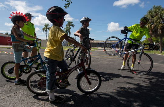 Oscar Rattenborg, a volunteer instructor, demonstrates how to execute an emergency stop during a bicycle class as part of the Wheel Lee Fun Summer Youth Program. The program aims to promote bicycle education and safety.