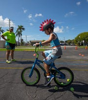 Wesley Pfrommer, 7, of Fort Myers, practices a bicycle obstacle course as part of the Wheel Lee Fun Summer Youth Program under the watchful eye of instructor Jodi Walborn. The program aims to promote bicycle education and safety.
