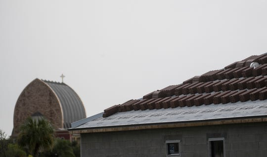 The roof of a new home is about to be installed in the town of Ave Maria. The oratory is in the background.