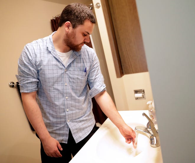 Austin Carter, Brown County public health sanitarian, checks for hot water during a routine inspection of a short-term rental property on Aug. 7, 2019 in Ashwaubenon, Wis.