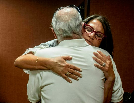 FILE - In this July 11, 2019 file photo, Tanya Gersh, a Montana real estate agent, embraces her father Lloyd Rosenstein following a hearing at the Russell Smith Federal Courthouse in Missoula. A Montana judge has ordered the publisher of a neo-Nazi website to pay Gersh over $14 million for encouraging his readers to harass her and her family. U.S. District Judge Dana Christensen on Thursday, Aug. 8, 2019 also ordered The Daily Stormer founder Andrew Anglin to permanently remove all posts, comments and images about Gersh, her husband and son. (Ben Allen/The Missoulian via AP, File)