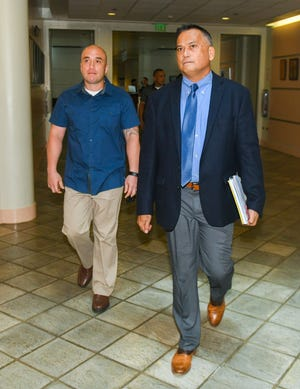 "Attorney Joaquin ""Jay"" Arriola Jr., right, with his client and former police officer, Mark Torre Jr., in the Guam Judicial Center in Hagåtña in this Aug. 8, 2019, file photo."