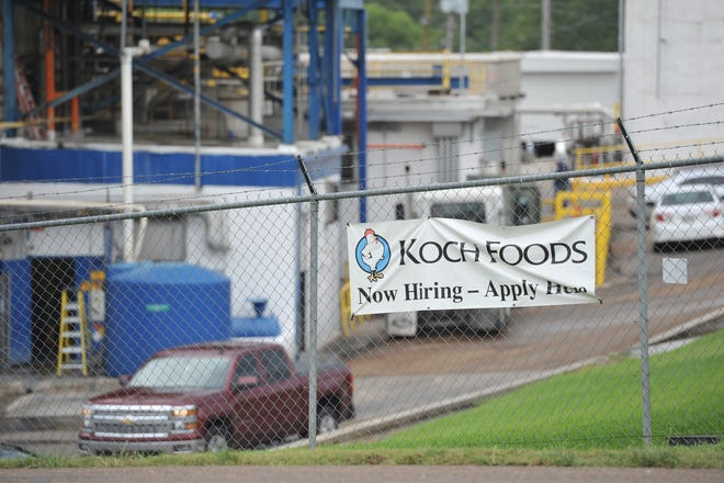 "Hanging on the chainlink fence surrounding Koch Foods in Morton, Mississippi, is a banner advertising ""Now hiring."" Koch was one of seven locations hit by U.S. Immigration and Customs officials across Mississippi Wednesday, Aug. 7, 2019, detaining 680 people."