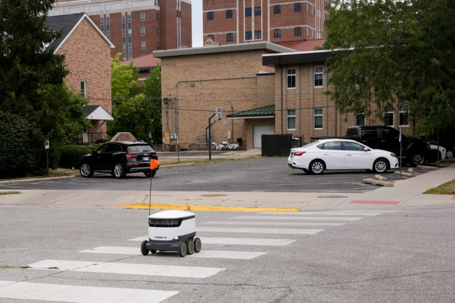 A Starship Technologies robot drives along the sidewalk on First st., Thursday, Aug. 8, 2019 in West Lafayette. The self-driving delivery robot is mapping the Purdue campus according to an employee.