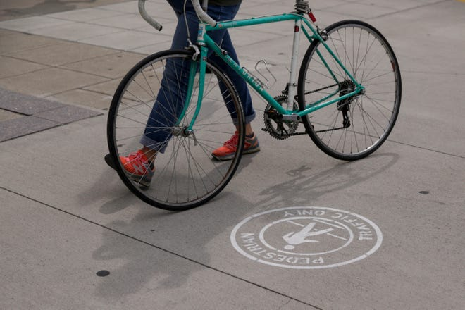 """A woman walks her bike past a """"pedestiran traffic only"""" icon on the State Street sidewalk, Thursday, Aug. 8, 2019 in West Lafayette."""