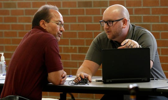 "Ed Sammler, left, from Pickerington, listens during his meeting with an assessor Thursday evening, Aug. 7, 2019, at Millersport Junior/Senior High School in Millersport. Sammler came to the Fairfield County Auditor's office's informal hearing with hopes of getting his assessed property value lowered. Sammler said the assessed value of his property increased 35% from 2016. ""You expect taxes and you expect increases not just 35% at once,"" he said. ""I know my pay hasn't gone up that much."""