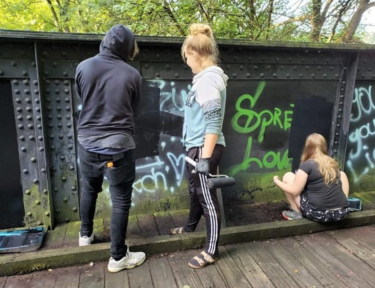 Volunteers work on painting over graffiti  at the Cenci Park bridge. School resource officers from the Fairfield County Sheriff's Office and teens in the juvenile court system are working together to clean up across the county.