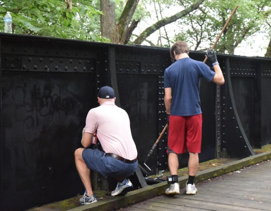Volunteers work on painting over graffiti  at the Cenci Park bridge. School resource officers from the Fairfield County Sheriff's Office's and teens in the juvenile court system are working together to clean up across the county.