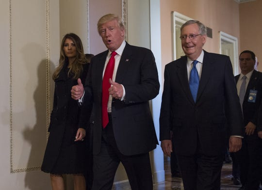 President-elect Donald Trump, flanked by his wife Melania and Senate Majority Leader Mitch McConnell of Ky., gives a thumbs-up while walking on Capitol Hill in Washington, Thursday, Nov. 10, 2016, after their meeting.