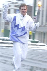 Tim Staudt seen Jan. 6, 2002 running with the Olympic Torch down Grand River Avenue in East Lansing. The veteran WILX-TV sports anchor has been a broadcaster for more than 50 years.
