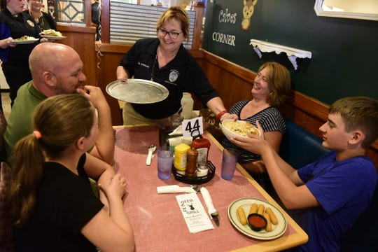 Ginger Antrician, the youth program coordinator for the Mansfield Police Department, hands an entree to Kaden Gilland, 14, during a fundraiser Thursday at the Reindeer Grill in Mansfield.