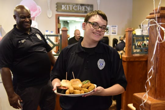 Samuel Bohnwagner, 14, a member of the explorer program at the Mansfield Police Department, carries a dish to a table at the Reindeer Grill during a fundraiser Thursday as Officer Orlando Chatman looks on.