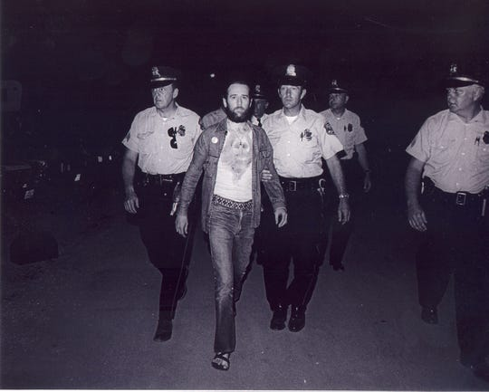 "George Carlin is escorted by officers after his 1972 arrest at Summerfest, for his bit about the ""Seven Words You Can't Say on Television."" The photo was among Mark Goff's more famous pictures."