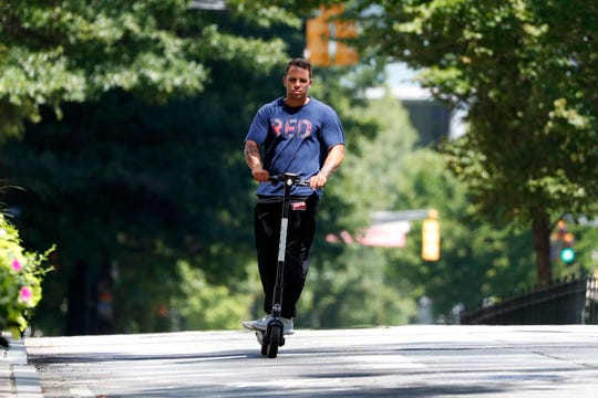 A man rides an electric scooter in Atlanta on Thursday.