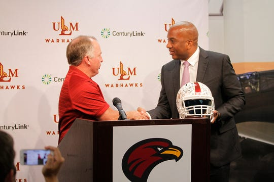 ULM football coach Matt Viator presents new Sun Belt Commissioner Keith Gill with a helmet signed by the Warhawks.
