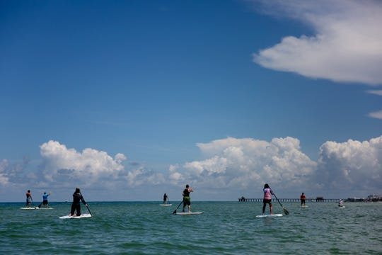 Participants paddle toward the pier during a stand up paddle board fitness class in Naples on Thursday, August 8, 2019.