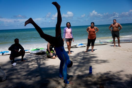 Simon Tracy demonstrates how to do a handstand during a stand up paddle board fitness class near Naples Pier in Naples on Thursday, August 8, 2019.