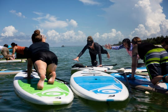 From left to right, Val Berube, Leslie Studwell, Katie Lang, and Sarah Layton participate in a stand up paddle board fitness class near Naples Pier in Naples on Thursday, August 8, 2019. The class, led by Simon Tracy, happens every Thursday, weather permitting, and spots can be booked through the Naples Kayak Company.