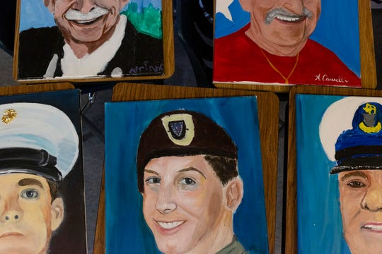 Painted portraits are displayed on tables on Wednesday, August 7, 2019, at the Community School of Naples.
