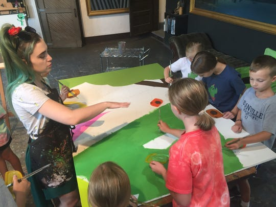 Instructor Sarah Gray directs Bryn Du Art Center camp students as they paint.