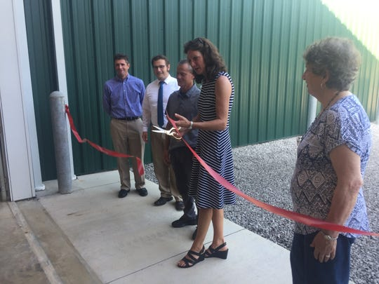 An official ribbon cutting of the new Village Service Complex is completed by (from left) council members Jeremy Johnson and Phil Demarest, Service Director Darren Willey, Mayor Melissa Hartfield and council member Jackie O'Keefe.