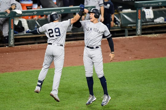 Gio Urshela #29 of the New York Yankees celebrates with Aaron Judge #99 after hitting a two-run home run in the sixth inning against the Baltimore Orioles at Oriole Park at Camden Yards on August 7, 2019 in Baltimore, Maryland.