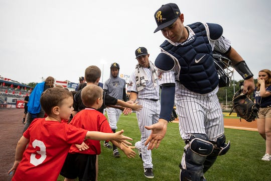 New York Yankees catcher Gary Sanchez, right, shakes hands with young fans before a Scranton/Wilkes-Barre RailRiders Triple-A baseball game against the Charlotte Knights in Moosic, Pa., Wednesday, Aug. 7, 2019. Sanchez is with the RailRiders on a rehab assignment.