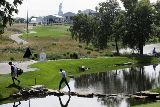 A golfer crosses water, by stepping on rocks at Liberty National Golf Club. Thursday, August 8, 2019