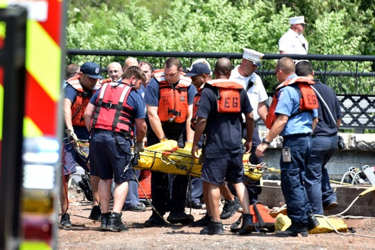 Rescue workers remove a body from the Passaic River near the bridge at West Broadway and Memorial Drive in Paterson on August 8, 2019.