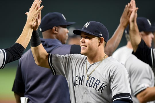 Gio Urshela #29 of the New York Yankees celebrates with teammates after a 14-2 victory against the Baltimore Orioles at Oriole Park at Camden Yards on August 7, 2019 in Baltimore, Maryland.