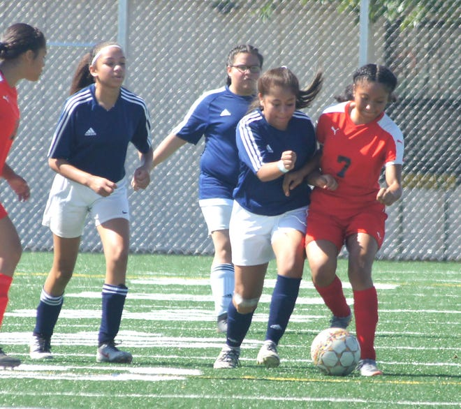 Lady 'Cat players plan to be more physical in a return match with the hatch Valley Bears at 10 a.m. on Saturday at the DHS Soccer Field. From left (in blue), Persephone Martin, Samantha Arteaga and Karysma Verdugo challenge Hatch defenders for the ball.