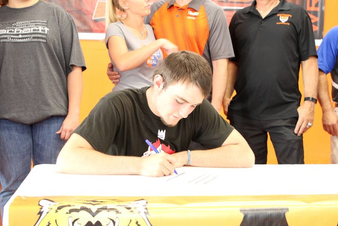 Aztec's Christian Robison signs his national letter of intent on Wednesday to continue his wrestling career at Northwest Kansas Technical College.