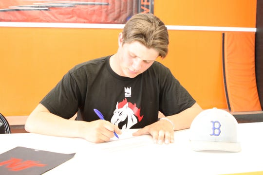 Bloomfield's Gerald Wiza signs his national letter of intent on Wednesday to continue his wrestling career at Northwest Kansas Technical College.