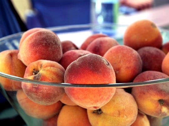 Peaches from a tree at Silver River Adobe Inn are seen, Thursday, April 8, 2019, at a booth at the Northwest New Mexico Local Food Summit.
