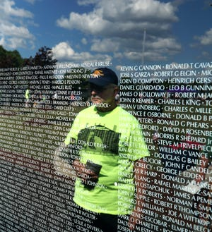 Vietnam War Army veteran Don Baker looks at some of the names etched into the surface of The Moving Wall on Aug. 8, 2019 at Livonia's Ford Field. The wall will be in Hamburg Township Thursday through Monday.