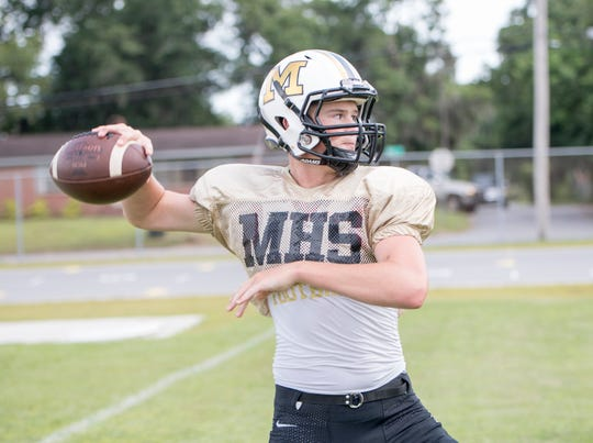 Quarterback Tyler Buchanan gets set to pass during football practice at Milton High School on Wednesday, August 7, 2019.