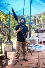 Pensacola bladesmith Wayne Meligan shows off a pole arm that he made at his Pirate Forge workshop Aug. 8.