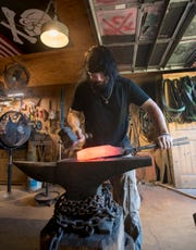 Pensacola bladesmith Wayne Meligan works on a blade at his Pirate Forge workshop Aug. 8.