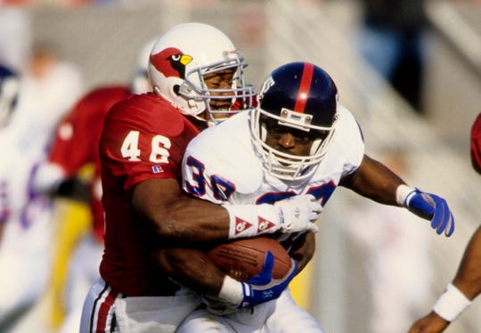 Phoenix Cardinals safety Tim McDonald (46) in tackles New York Giants running back Dave Meggett (30) during a game on Dec 12, 1992 at Sun Devil Stadium.